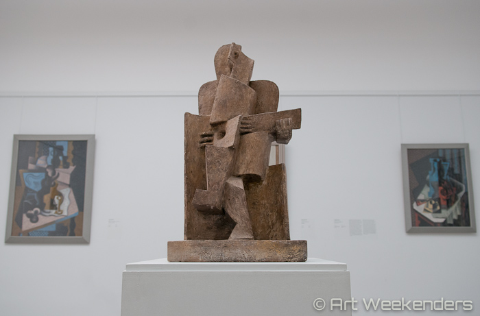 Sitting man with guitar by Jacques Lipchitz.
